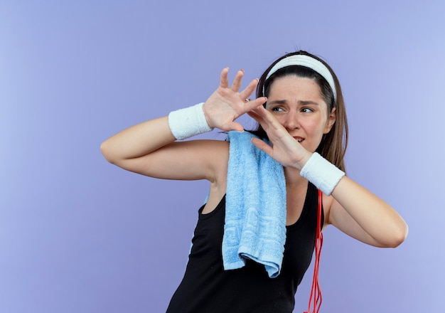 Mulher jovem fitness com bandana e toalha no ombro com medo de fazer gesto de defesa com as mãos em pé sobre a parede azul