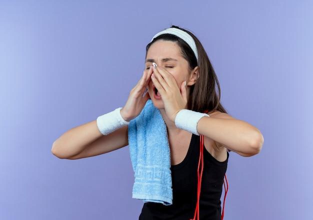 Mulher jovem fitness com bandana e toalha no ombro, gritando ou chamando alguém com as mãos perto da boca, em pé sobre a parede azul