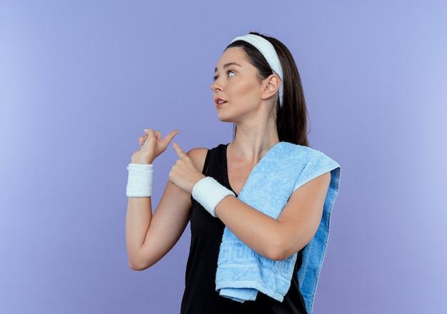 Mulher jovem fitness com bandana e toalha no ombro, olhando para o lado, apontando para trás, em pé sobre um fundo azul