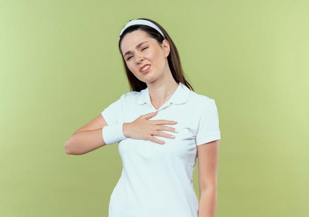 Mulher jovem fitness com bandana parecendo doente, segurando a mão no peito, sentindo desconforto em pé sobre a parede de luz
