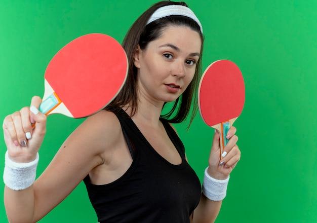 Mulher jovem fitness com bandana segurando raquetes de tênis de mesa, olhando para a câmera com expressão confiante em pé sobre fundo verde