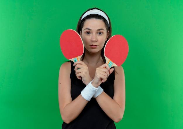 Mulher jovem fitness com bandana segurando raquetes de tênis de mesa, olhando para a câmera com o rosto sério, cruzando as mãos em pé sobre o fundo verde
