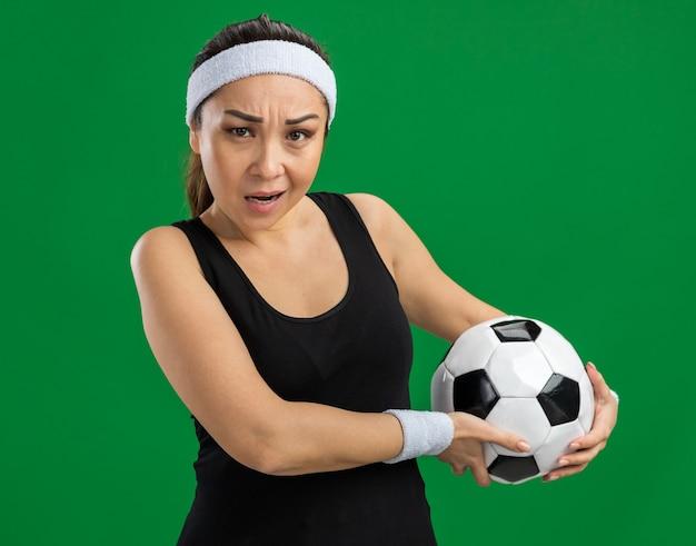 Mulher jovem fitness com bandana segurando uma bola de futebol e cara séria
