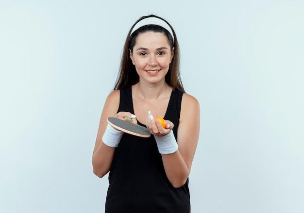 Mulher jovem fitness com bandana segurando uma raquete e uma bola de tênis de mesa, olhando para a câmera sorrindo alegremente em pé sobre um fundo branco