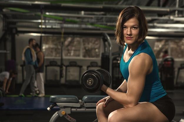 Mulher jovem fitness com corpo tonificado, fazendo exercícios de peso com halteres na academia