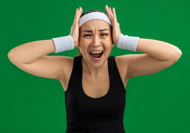 Mulher jovem fitness com faixa para a cabeça e braçadeiras, gritando e se sentindo frustrada com as mãos na cabeça em pé sobre a parede verde