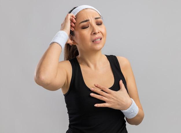 Mulher jovem fitness com faixa para a cabeça e braçadeiras, sentindo-se indisposta tocando a cabeça em pé sobre uma parede branca