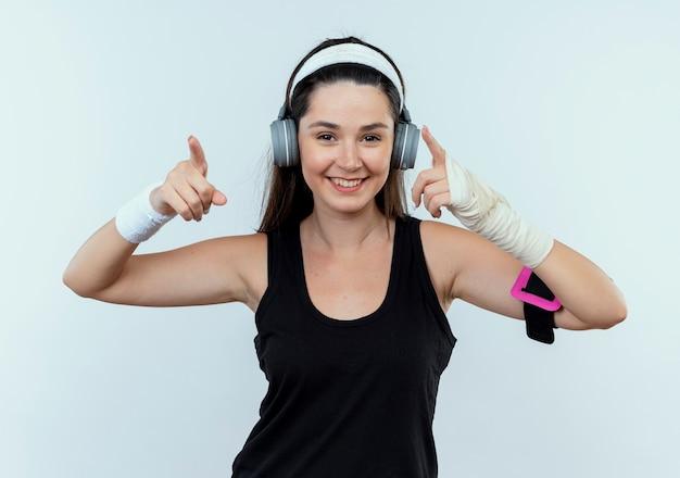 Mulher jovem fitness com fita para a cabeça com fones de ouvido e braçadeira de smartphone olhando para a câmera sorrindo com uma cara feliz apontando com os dedos indicadores para o lado, de pé sobre um fundo branco