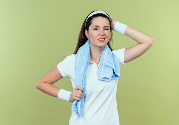Mulher jovem fitness com fita para a cabeça com uma toalha ao redor do pescoço, olhando para a câmera, confusa com a mão na cabeça por engano em pé sobre fundo claro