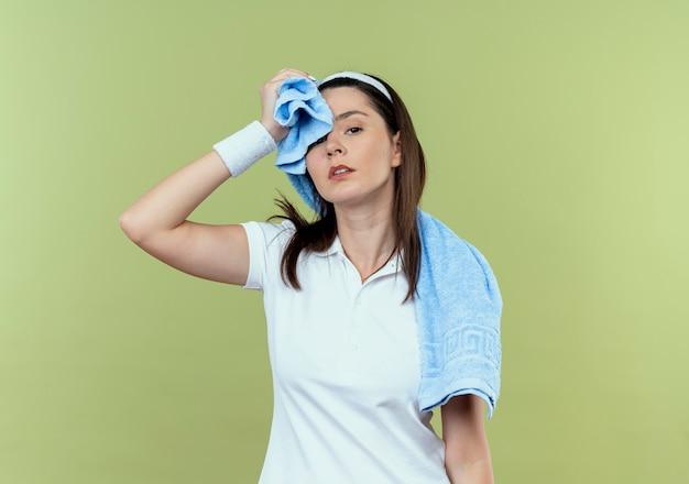 Mulher jovem fitness com fita para a cabeça com uma toalha ao redor do pescoço secando a testa, parecendo cansada e exausta em pé sobre um fundo claro