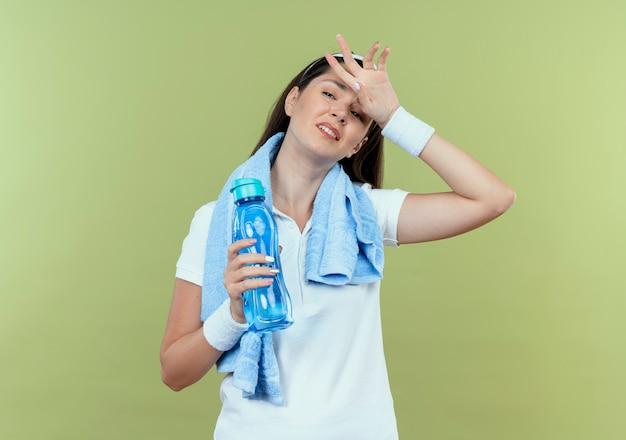 Mulher jovem fitness com fita para a cabeça com uma toalha em volta do pescoço segurando uma garrafa de água, parecendo cansada e exausta após o treino em pé sobre a parede de luz