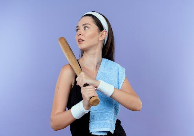 Mulher jovem fitness com fita para a cabeça com uma toalha no ombro, segurando o taco de beisebol, olhando para o lado com uma cara séria em pé sobre um fundo azul