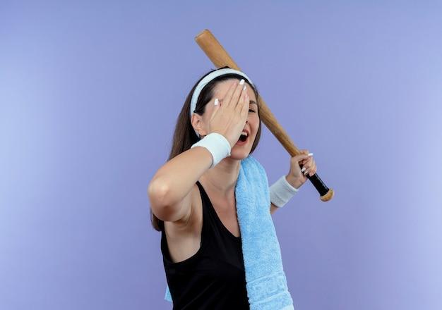 Mulher jovem fitness com fita para a cabeça com uma toalha no ombro segurando um taco de beisebol cobrindo um dos olhos com uma mão sorrindo em pé sobre um fundo azul