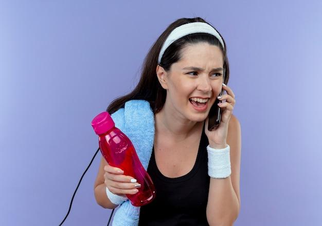 Mulher jovem fitness com fita para a cabeça com uma toalha no ombro segurando uma garrafa de água e falando no celular com uma expressão irritada em pé sobre a parede azul