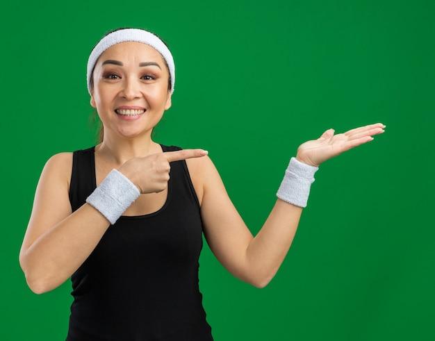 Mulher jovem fitness com fita para a cabeça e braçadeiras com sorriso no rosto apresentando com o braço da mão cópia sapce apontando com o dedo indicador para o lado