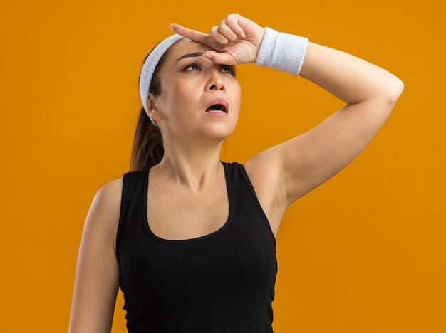 Mulher jovem fitness com fita para a cabeça e braçadeiras, olhando para cima com a mão na cabeça, cansada e com excesso de trabalho em pé sobre a parede laranja