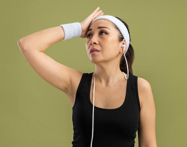Mulher jovem fitness com fita para a cabeça e braçadeiras olhando para o lado intrigada com a mão na cabeça em pé sobre a parede verde