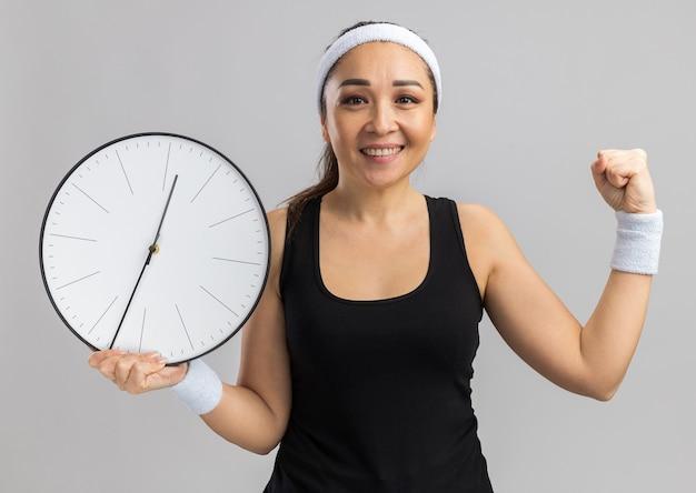 Mulher jovem fitness com fita para a cabeça e braçadeiras segurando um relógio de parede com um sorriso no rosto cerrando o punho em pé sobre a parede branca