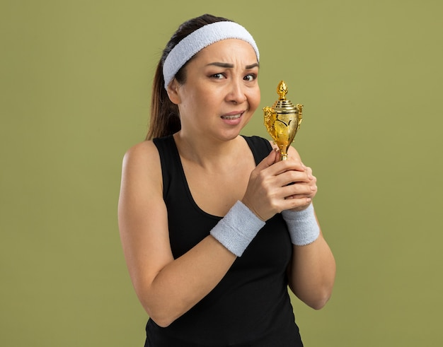 Mulher jovem fitness com fita para a cabeça e braçadeiras segurando um troféu com expressão cética