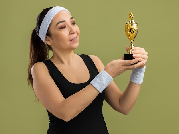 Mulher jovem fitness com fita para a cabeça e braçadeiras segurando um troféu olhando para ele feliz e satisfeita
