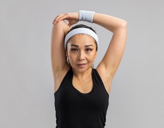 Mulher jovem fitness com fita para a cabeça e braçadeiras, sorrindo confiante, esticando as mãos em pé sobre uma parede branca