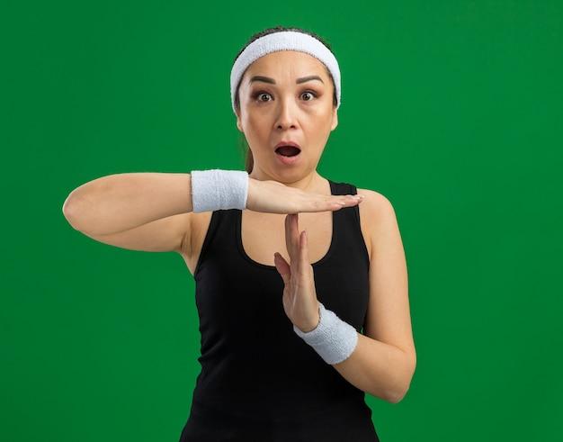 Mulher jovem fitness com fita para a cabeça e braçadeiras surpresa fazendo gesto de pausa com as mãos em pé sobre a parede verde
