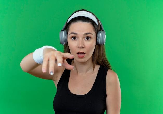 Mulher jovem fitness com fita para a cabeça e fones de ouvido, olhando para a câmera, confundindo a expressão com o braço estendido sobre um fundo verde.