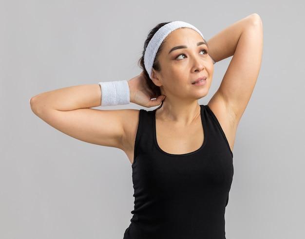 Mulher jovem fitness com fita para a cabeça olhando para o lado, esticando as mãos, prontas para o treino, em pé sobre uma parede branca