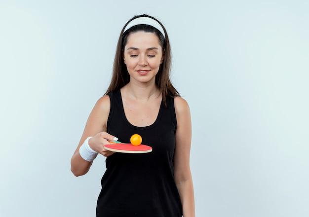 Mulher jovem fitness com fita para a cabeça, segurando a raquete e a bola para tênis de mesa, sorrindo confiante em pé sobre um fundo branco