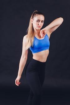 Mulher jovem fitness com mãos enluvadas, apresentando músculos abdominais tensos