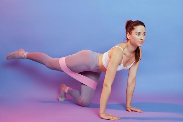 Mulher jovem fitness com musculatura bem desenvolvida exercitando os músculos glúteos, levanta a perna, atleta feminina estando em boa forma em roupa esportiva justa, usa elástico durante o treino focado no bumbum