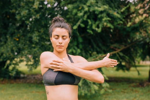 Mulher jovem fitness com os olhos fechados, esticando as mãos no parque