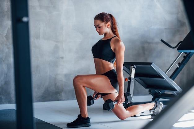 Mulher jovem fitness com tipo de corpo magro e com roupas esportivas pretas está no ginásio.
