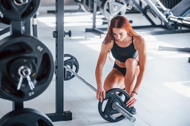Mulher jovem fitness com tipo de corpo magro e roupas esportivas pretas está no ginásio com barra.