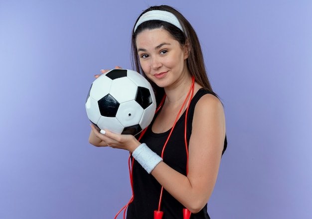 Mulher jovem fitness com uma bandana na cabeça e pular corda no pescoço segurando uma bola de futebol e sorrindo em pé sobre a parede azul