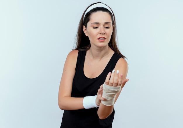 Mulher jovem fitness com uma bandana olhando para o pulso enfaixado, sentindo dor em pé sobre um fundo branco