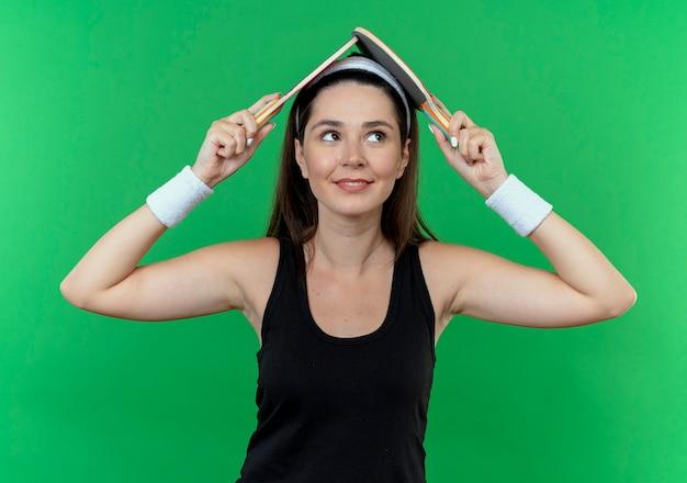 Mulher jovem fitness com uma bandana segurando duas raquetes de tênis de mesa na cabeça, sorrindo em pé sobre um fundo verde