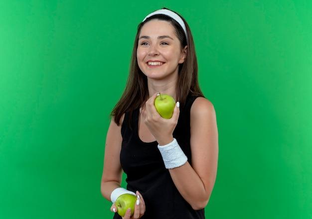 Mulher jovem fitness com uma bandana segurando maçãs verdes sorrindo com uma cara feliz em pé sobre a parede verde