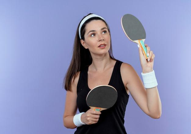 Mulher jovem fitness com uma bandana segurando raquetes de tênis de mesa, olhando para o lado com uma expressão confiante em pé sobre um fundo azul