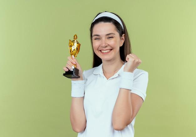 Mulher jovem fitness com uma bandana segurando seu troféu, feliz e animada, cerrando o punho em pé sobre a parede de luz