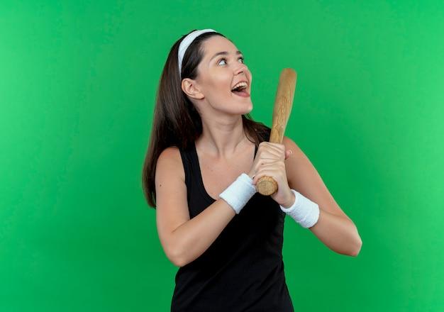 Mulher jovem fitness com uma bandana segurando um taco de beisebol, olhando de lado feliz e animada em pé sobre um fundo verde