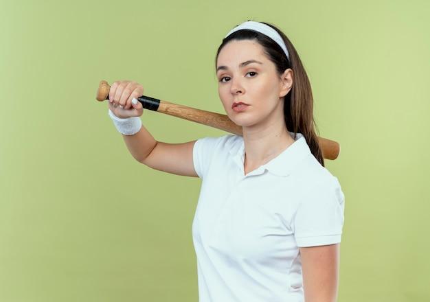 Mulher jovem fitness com uma bandana segurando um taco de beisebol, olhando para a câmera com uma expressão séria e confiante em pé sobre um fundo claro