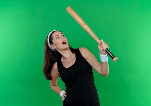 Mulher jovem fitness com uma bandana segurando um taco de beisebol olhando para ele confusa em pé sobre um fundo verde