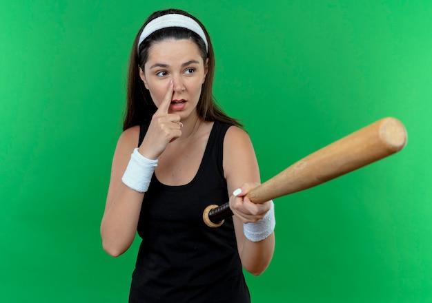 Mulher jovem fitness com uma bandana segurando um taco de beisebol, olhando para o lado, apontando com o dedo ou o nariz em pé sobre um fundo verde