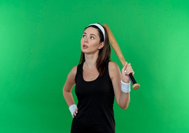 Mulher jovem fitness com uma bandana segurando um taco de beisebol olhando para o lado com uma expressão pensativa em pé sobre um fundo verde