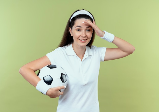 Mulher jovem fitness com uma bandana segurando uma bola de futebol, parecendo confusa com a mão na cabeça por erro em pé sobre parede de luz