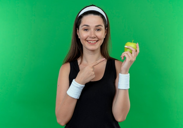 Mulher jovem fitness com uma bandana segurando uma maçã verde apontando com o dedo para ela, sorrindo alegremente em pé sobre um fundo verde