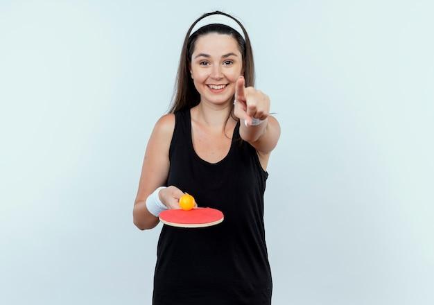 Mulher jovem fitness com uma bandana segurando uma raquete e uma bola de tênis de mesa apontando com o dedo para a câmera e sorrindo alegremente em pé sobre um fundo branco
