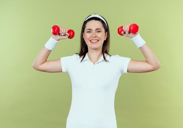 Mulher jovem fitness com uma faixa na cabeça e malhando com halteres esticados em pé sobre a parede de luz