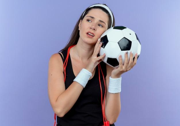 Mulher jovem fitness com uma faixa na cabeça e pular corda em volta do pescoço segurando uma bola de futebol, olhando de lado o pneu e entediada em pé sobre a parede azul